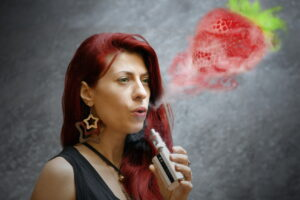 woman smoking electronic cigarette outdoor office building  - iStock_000069764257_Medium