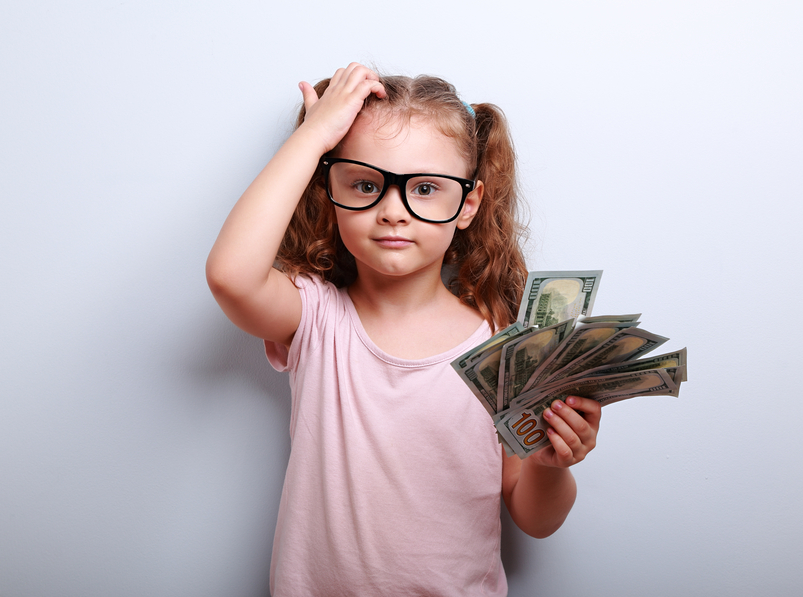Small professor in eye glasses scratching head, holding money and thinking how earring more. Kid have a big idea. Emotional portrait on blue background with empty copy space