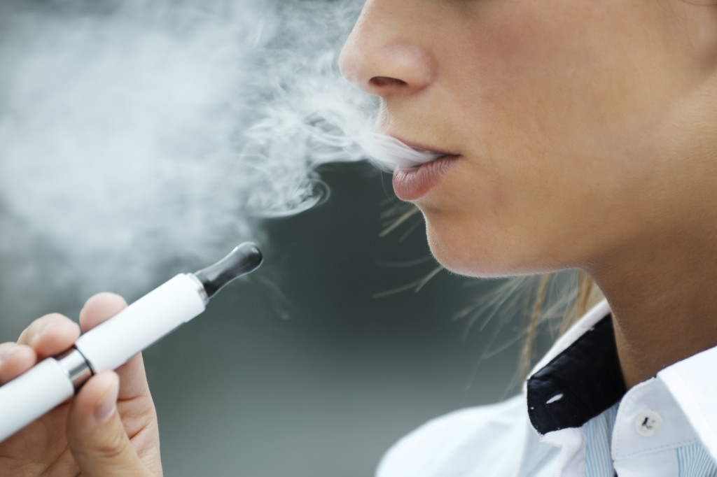 closeup of woman smoking e-cigarette and enjoying smoke.
